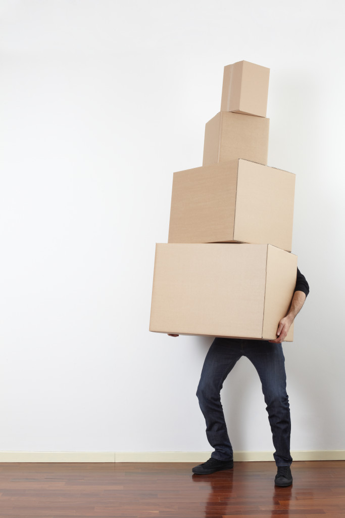 Man lifting cardboard boxes in apartment, moving day