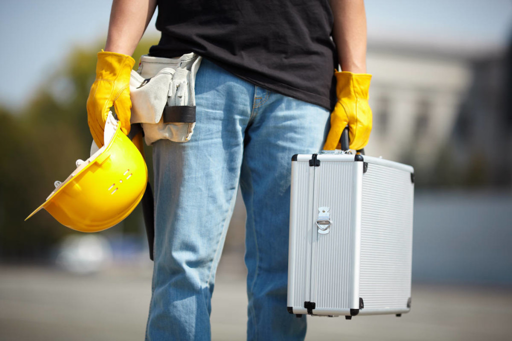 hands of worker in yellow gloves with hardhat and aluminium tool case, selective focus